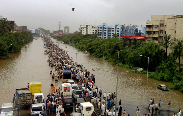 Indian commuters walk through floodwaters past stranded motor vehicles after heavy torrential rains paralysed the city of Mumbai in July 2005. Photo: Sebastian D'Souza / AFP / Getty Images