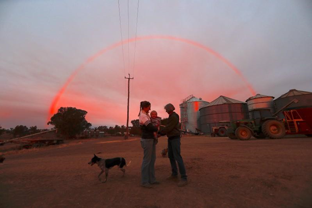 Farmer Tom Wollaston's wife Margo talks with her daughter Natasha and her granddaughter Abbey as a rainbow forms above them at sunset on their drought-affected property, located west of the town of Tamworth, in north-western New South Wales in Australia, 2 June 2018. Photo: David Gray / REUTERS