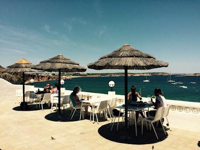 Noen bord på en terrasse med havet i bakgrunnen.