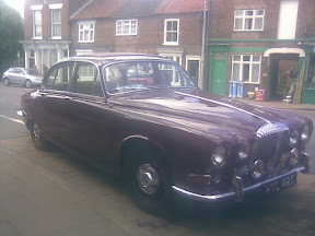 old burgundy coloured limousine parked on street