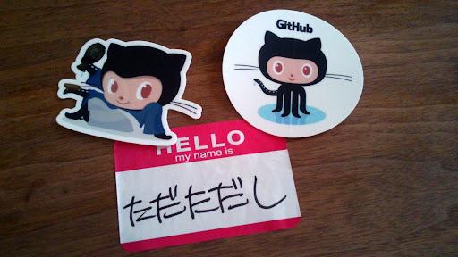 [写真]名札とOctcatステッカー。Kaigiのステッカー、やっぱりキャラクタものは日本でデザインすべきだよなと思う。かわいい。