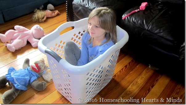 Emma in laundry basket at Homeschooling Hearts & Minds