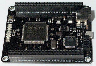 The Mojo FPGA board. The Spartan-6 FPGA chip dominates the board.