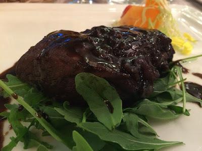 Et biffstykke med mørk saus og noen salatblader i forgrunnen.