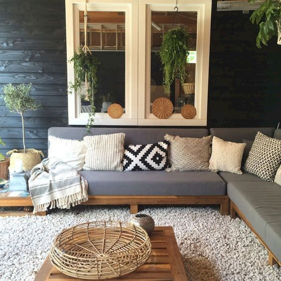 outdoor living room with grey sofa pillows coffee table and blankets