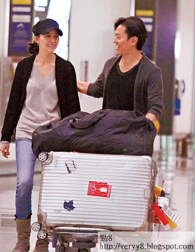 攞完行李,手推行李車的伊健,另一隻手則搭實老婆。