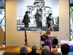 Musikerin und Zuhörer vor Projektionswand mit Hiroshima-Bild.