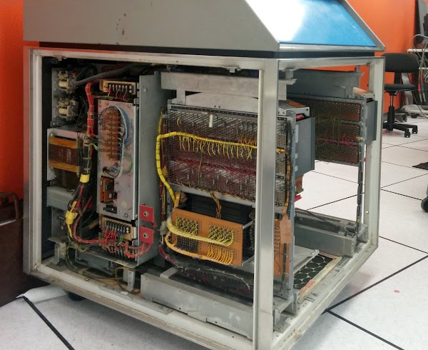 Inside the IBM 1406 Storage Unit. At the left are the power supplies, including a 450W ferro-resonant regulator. The 8K core memory is at the right, connected by yellow wire bundles to the control circuitry above.