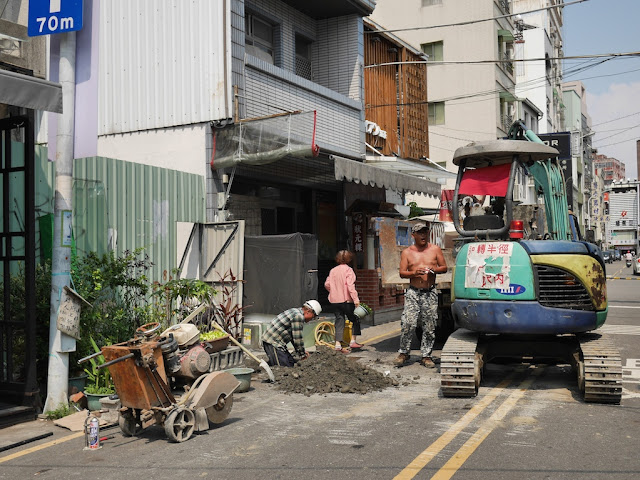 woman carrying a potted plant away from construction work by the Taiwan Water Corporation at Zhengxing Street in Tainan
