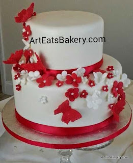Two tier white fondant modern wedding cake design with red ribbons,  edible butterflies and flowers