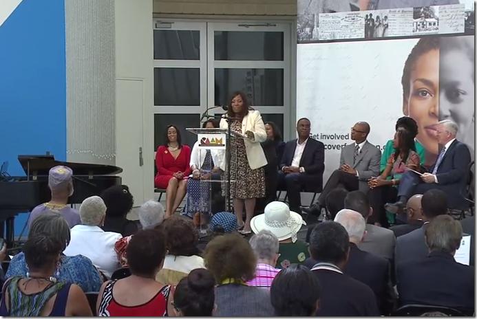 Jannah Scott在弗里森说话'S局索引项目新闻发布会。点击查看YouTube。