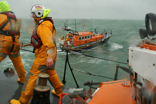 It's a swell time! Poole ALB high on the swell in a training exercise with Swanage lifeboat - note Poole crew are attached by their safety lines on deck - 26 January 2014.  Photo credit: RNLI Poole/Rob Inett