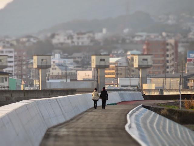 曽根干潟に注ぐ竹馬川沿いを歩くカップル