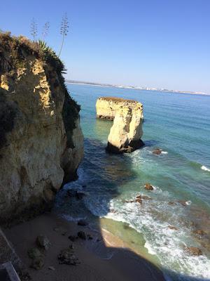 En skyggefull klippestrand med store steiner og bølger mot stranden.