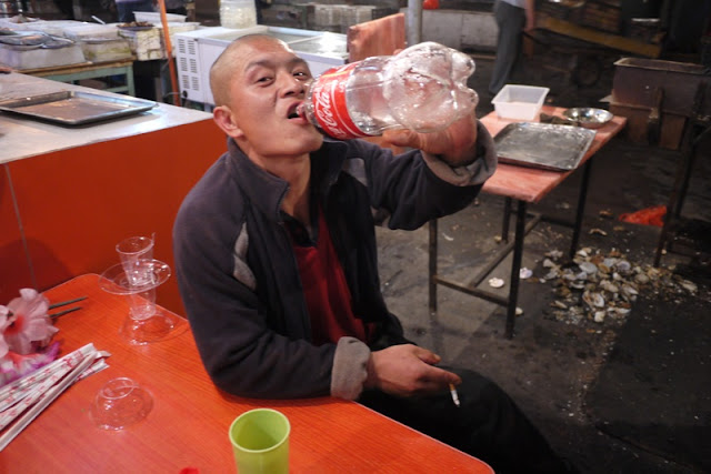 man drinking from two liter bottle of Coca-cola