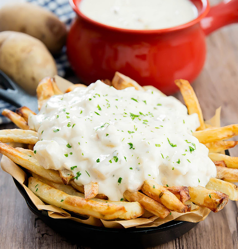 a close up of french fries topped with chowder
