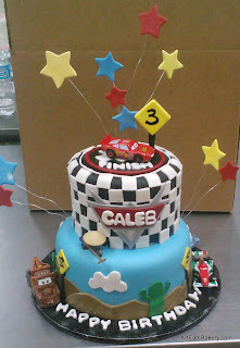 Custom modern kid's creative Cars birthday cake design with edible stars, cactus, street signs and checkered flag top tier. The cars are toys for the birthday boy