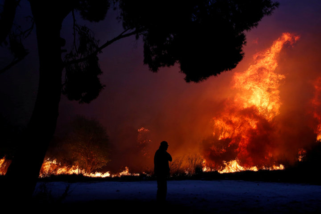 A wildfire burns near Athens, Greece, on 23 July 2018. Photo: Costas Baltas / Reuters