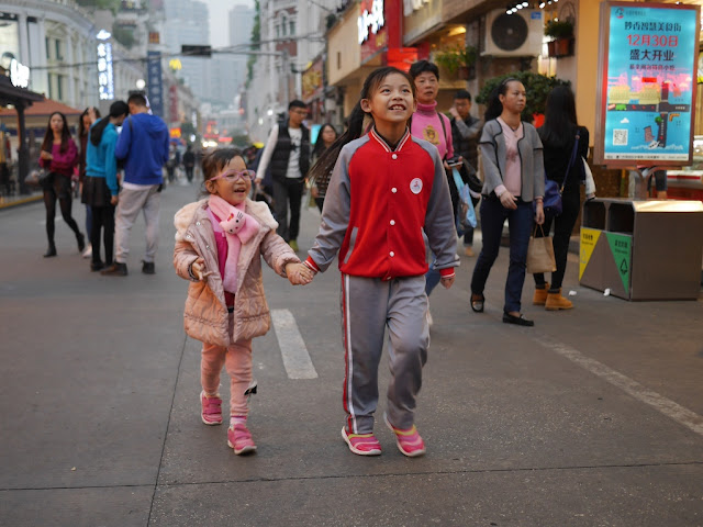 two girls holding hands walking down Xiamen's Zhongshan Road Pedestrian Street