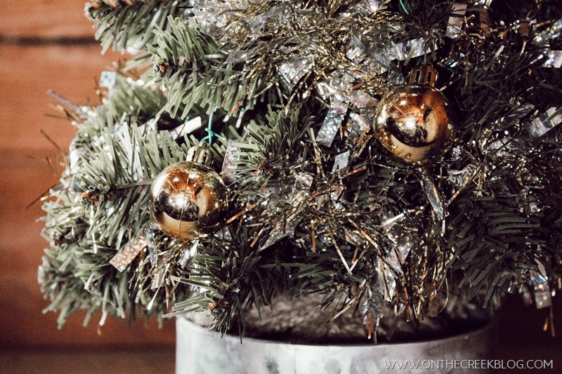 Decorating a small tree for Christmas using a tiny galvanized pot & Dollar Tree ornaments, tinsel & lights!