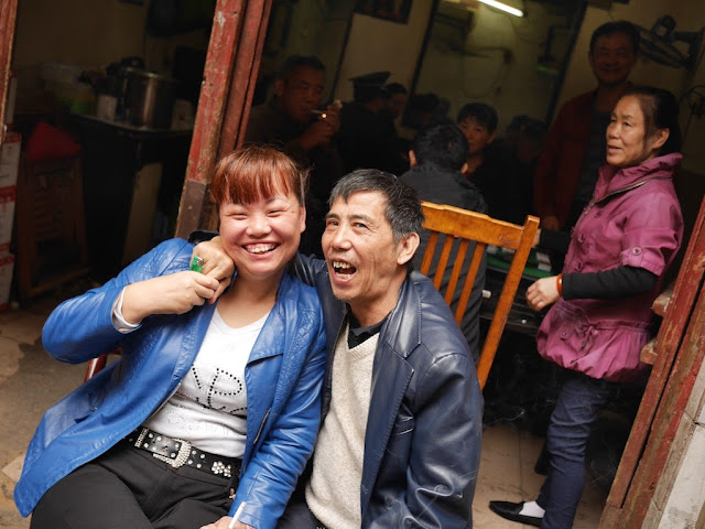 woman and man posing outside for a photo in front of a room filled with mahjong players