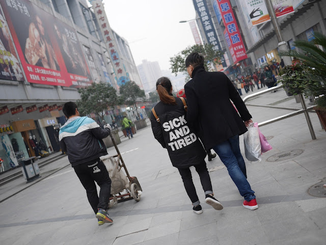 "young woman in Shanghai wearing a coat with the words ""SICK AND TIRED"" on its back"
