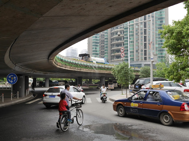 a water truck being used to water the plants alongside an overpass in Hengyang