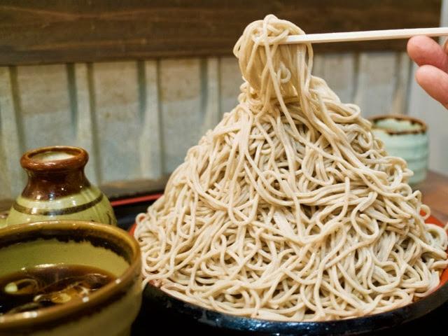 富士山盛りの頂上から蕎麦を持ち上げている