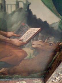 En este cuadro el pintor ha sacrificado la proporción del tamaño de las letras con el libro para que se aprecie que contiene letras. Por el toro supongo que será San Lucas Evangelista.