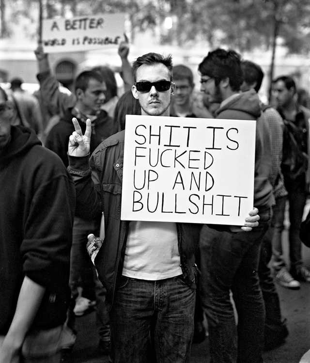 "A young protester holds a sign that reads, ""Shit is fucked up and bullshit"". ""On top of all the inequality in our country, we are going overseas and murdering people. Everything was rigged, and while we were all complaining that the system is corrupt, we just went on with our lives, feeling powerless. Of course I still have class rage. I have never had money."" —Mickey Smith, Occupy Wall Street protester, photographed in 2011 and interviewed in 2018. Photo: Accra Shepp"