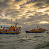 Three lifeboats against a dappled sky backdrop. Photo credit: Andy Lyons, Swanage RNLI