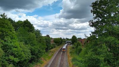 Train approaching, trees and clouds viewed from road bridge