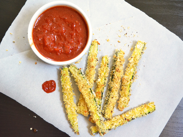 Golden baked zucchini fries on parchment paper next to a bowl of marinara sauce.