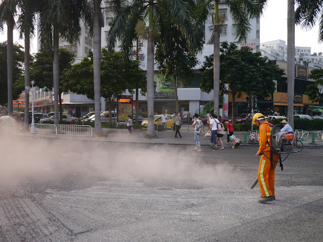 people walking by a man using a blower to move gravel and creating a large dust cloud on a street in Zhuhai