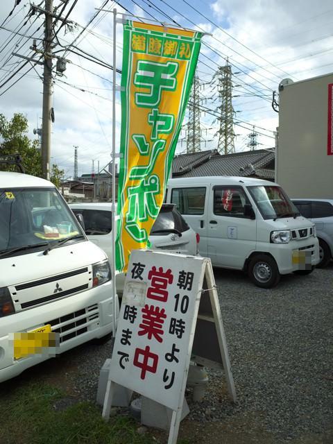 店頭の駐車場に立てられた営業時間の看板とチャンポンのノボリ