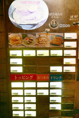 At Shin Yokohama Ramen Museum, similar to many ramen shops, at each place you order from a machine. Here luckily plastic laminated menus explain the dishes in Japanese, Chinese, Thai, and English with corresponding numbers to match the machine you will insert money and get your food ticket from.