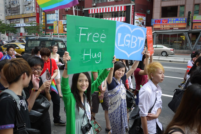 young women hold signs that say free hug and LGBT