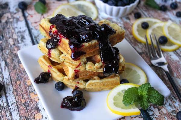 Lemon Poppyseed Waffles With Blueberry Sauce Drizzled On Top.