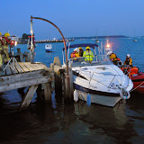 A view of the motor cruiser at Lake Pier, with lifeboat crew and fire crew inspecting the vessel - 31 October 2014. Photo credit: RNLI Poole