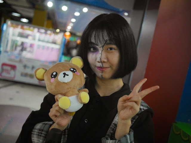 young woman wearing face paint and holding a small stuffed bear in Shaoguan