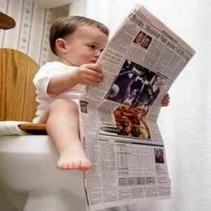 Bebê lendo jornal no banheiro