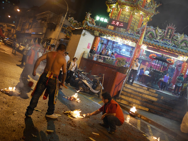 man holding a flail and another lighting a fire for a ceremony at the Chang Qing Temple (長慶廟) in Taipei