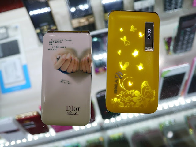 a Dlor flip phone with a poem and an image of two hands and two rings and a yellow JYING flip phone with a scene of butterflies lit up and a digital clock