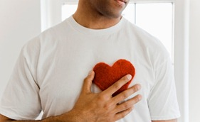 Man holding heart shape on chest