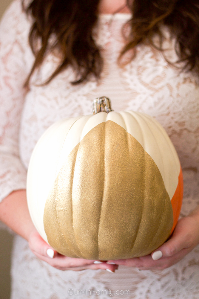 gold painted pumpkin in woman's arms