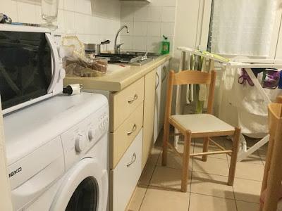 Et rotete kjøkken med vaskemaskin, komfyr og oppvaskkum.