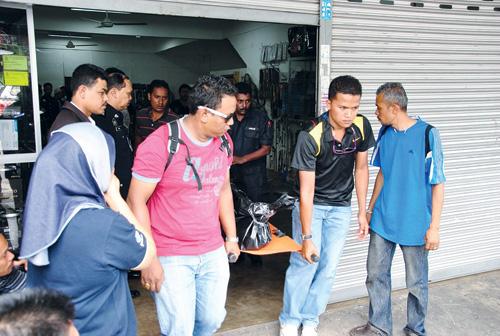 ANGGOTA polis mengangkat mayat Raja Dzulhairi Raja Ali yang dipercayai mati dibunuh dalam sebuah kedai aksesori kenderaan di Taman Cindai, Jalan Kuala Ketil, Sungai Petani, Kedah, semalam. - UTUSAN/OPAT RATTANACHOT
