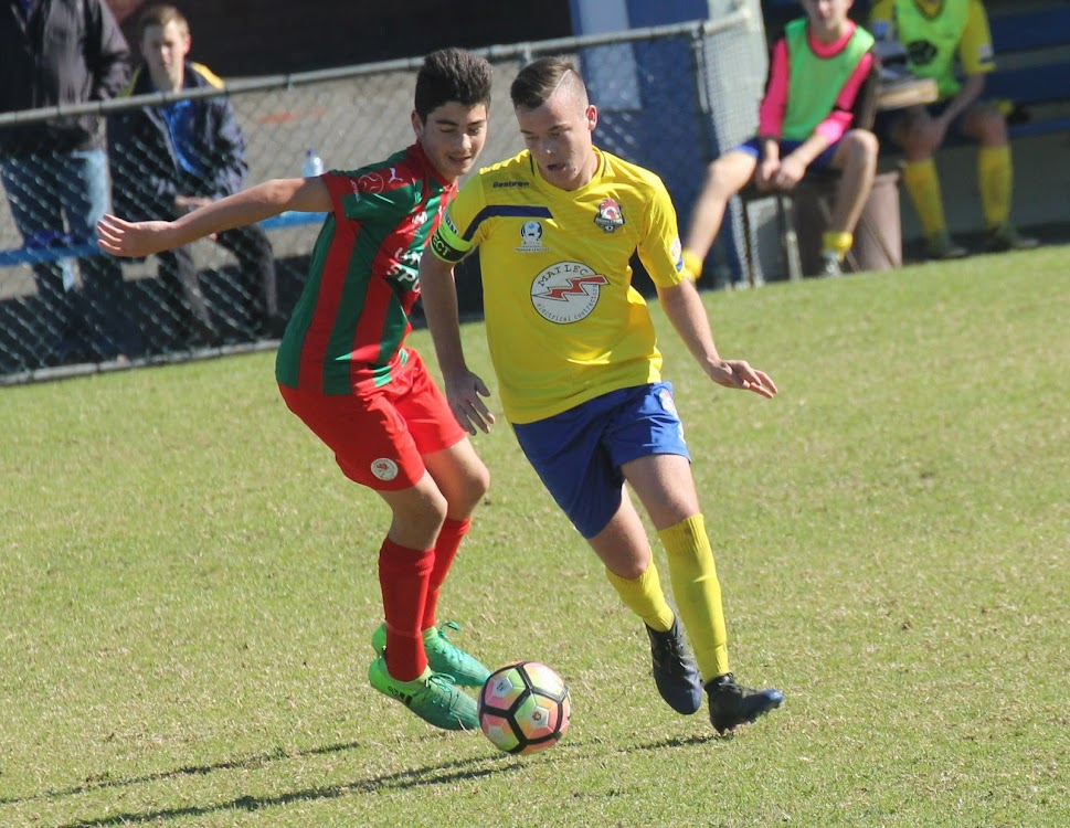 Cooper Brayshaw, right, skips past an Adamstown Rosebuds player in round 17 of the Northern NSW National Premier League under-18 competition on Sunday. Brayshaw is the captain of his side - the Lake Macquarie Roosters.