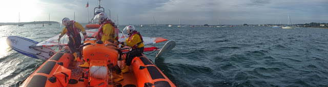 The ILB crew secure the windsurf kit to the back of the ILB. 28 September 2013. Photo credit: RNLI / Rob Inett