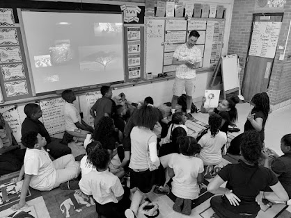 Ian Tadashi Moore reading to a classroom of young students